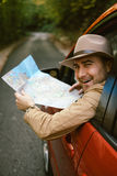 Traveler  man with hat  looking map near car in autumn forest Stock Images