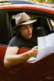 Traveler  man with hat  looking map near car in autumn forest Royalty Free Stock Photos