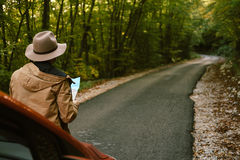 Traveler  man with hat  looking map near car in autumn forest Stock Photo