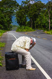 Traveler man in the hat on the road with a suitcase going on res Royalty Free Stock Photo