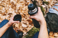 Traveler man holding thermos in autumn forest Royalty Free Stock Image