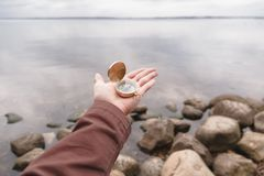 A traveler man holds a compass in his hand, standing on a stone beach. Royalty Free Stock Photos