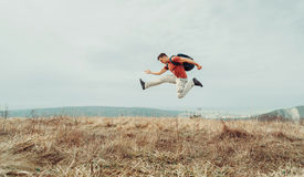 Traveler man jumping on nature. Happy hiker young man with backpack jumping on nature Royalty Free Stock Photo