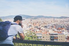 Traveler man looking on a big city, travel and active lifestyle concept.Bearded Tourist Man with backpack enjoy. Beautiful city view on sunset stock image