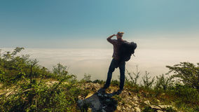 A traveler man looks into the distance standing on top of a mountain. Travel lifestyle Stock Photos