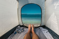 Traveler Man Lying In Tent With A View Of Sea Summer Beach Holiday Vacation Concept. View Of Legs. Point Of View Shot Stock Photo