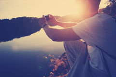 Traveler man making photo above the lake at sunset with his mobile phone Royalty Free Stock Photos
