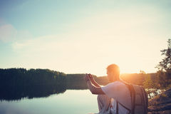 Traveler man making photo at the lake at sunset with his mobile phone Stock Photo