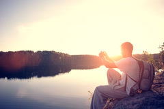 Traveler man making photo at sunset with his mobile phone sitting on the cliff above the lake Royalty Free Stock Photos
