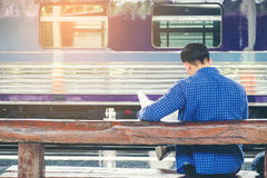 Traveler man with map and waits train on railway platform.  Stock Images