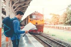 Traveler man with map and waits train on railway platform.  Royalty Free Stock Photos