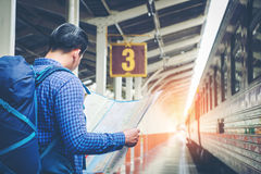 Traveler man with map and waits train on railway platform.  Stock Photos