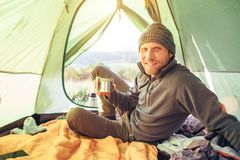 Traveler man meet morning in camping tent with cup of tea stock images