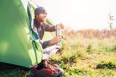 Traveler man meet morning in tent with hot tea royalty free stock photos