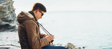 Traveler man with photo camera sitting on coast. Traveler young man with photo camera sitting on coast near the sea Stock Image