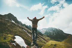 Traveler Man raised hands standing on cliff mountains. Adventure travel lifestyle concept summer vacations outdoor euphoria happy emotions Stock Photo