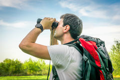 Traveler man with red backpack looks through a binoculars. Hiking concept Stock Photography