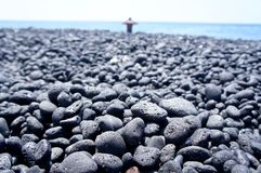 Traveler man relaxing on a black pebble beach on the Big Island of Hawaii. Blurred out traveler man relaxing on a black pebble beach on the Big Island of Hawaii Royalty Free Stock Photo