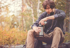 Traveler Man relaxing in forest with thermos, backpack and photo camera Royalty Free Stock Photos