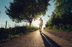 Traveler man silhouette on sunset road Stock Photos