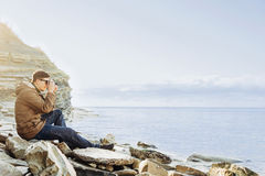 Traveler man sitting on coastline and taking photographs Royalty Free Stock Images