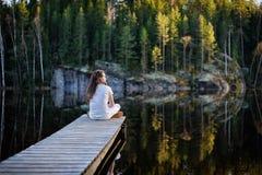 Traveler man sitting by a lake Stock Images