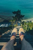 Traveler Man Sitting On Steps Of Stairs Coast Above Sea, View Of Legs. Point Of View Shot Royalty Free Stock Image