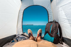 Traveler Man Sitting In A Tourist Tent by The Sea Summer Beach Holiday Vacation Concept. View Of Legs. Point Of View Shot Royalty Free Stock Photo