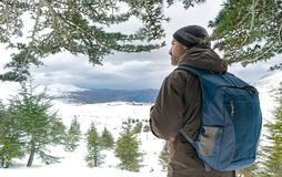 Traveler man in the snowy mountains royalty free stock image