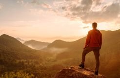 Traveler man standing on top of rock in the mountains. stock photo