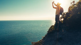 Traveler man stands on the top and takes pictures of sea on cell phone camera during sunset Royalty Free Stock Photo