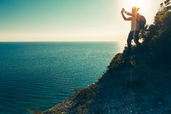 Traveler man stands on the top and takes pictures of sea on cell phone camera during sunset Stock Photography