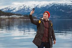 Traveler man taking self-portrait a photo with a smartphone. Tourist in a yellow backpack standing on a background of a stock images