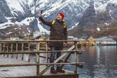 Traveler man taking self-portrait a photo with a smartphone. Tourist in yellow backpack standing on a background of a royalty free stock photo