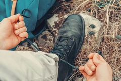 Traveler man tying shoelaces on nature Stock Photography
