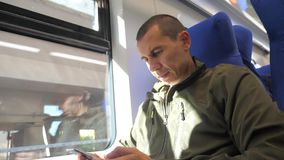 Traveler man unknown sitting by the window middle-aged smartphone in the subway railway train writes sms to social media