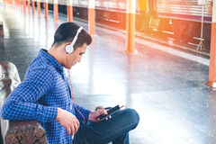 Traveler Man using tablet and headphone waiting for train on the. Station Stock Image