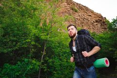 Traveler man walking with backpack in rocky mountains. Travel concept stock photos