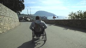 Traveler Man In Wheelchair Walk By Road stock footage