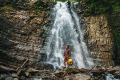Traveler man with a yellow backpack standing on the background of a waterfall. Travel lifestyle concept. stock photography