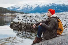 Traveler man with a yellow backpack wearing a red hat sitting on the shore on the background of mountain and lake. Space royalty free stock photo