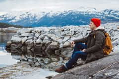 Traveler man with a yellow backpack wearing a red hat sitting on the shore on the background of mountain and lake. Space. For your text message or promotional royalty free stock photography