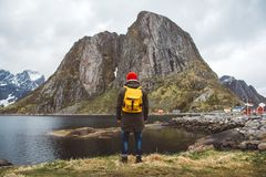 Traveler man with a yellow backpack wearing a red hat standing on the background of mountain and lake. Travel lifestyle royalty free stock images