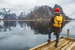 Traveler man with a yellow backpack wearing a red hat standing on the background of mountain and lake wooden pier. Travel lifestyle concept. Shoot from the stock image