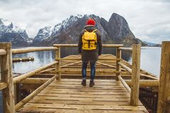 Traveler man with a yellow backpack wearing a red hat standing on the background of mountain and lake wooden pier stock photo