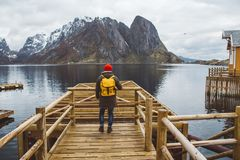 Traveler man with a yellow backpack wearing a red hat standing on the background of mountain and lake wooden pier. Travel lifestyle concept. Shoot from the stock photos