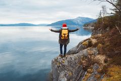 Traveler man with a yellow backpack wearing a red hat standing on a rock hands on the side on the background of mountain stock image