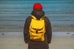 Traveler man with a yellow backpack wearing a red hat standing on a sandy beach on the background of the sea. Shoot from. The back stock photo