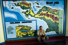 The traveler at a map. INDONESIA, NEW GUINEA, JAYAPURA - JANUARY 21: . The traveler sits at a map of New Guinea. January 21 2009. New Guinea, Jayapura stock image