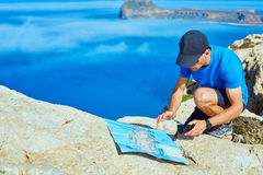 Traveler with map. Male traveler with backpack and map standing on the cliff against sea and blue sky at early morning Royalty Free Stock Images